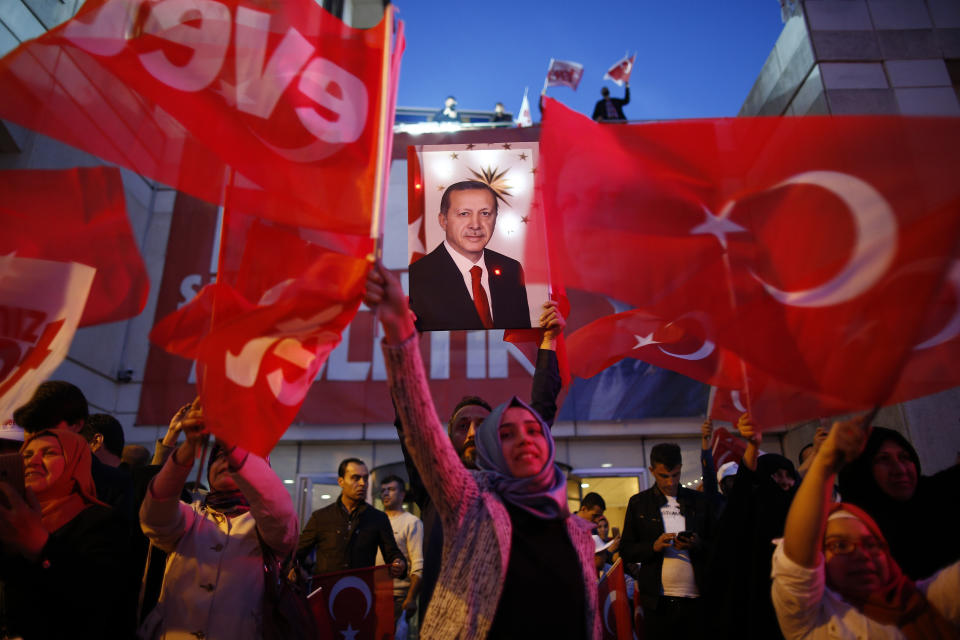 <p> Supporters of Justice and Development party (AK) wave Turkish flags and hold a poster of Turkish President Recep Tayyip Erdogan outside its offices in Istanbul, Sunday, April 16, 2017. Voting has ended in Turkey's historic referendum on whether to approve constitutional changes that would greatly expand the powers of Erdogan and the result will determine Turkey's long-term political future and will likely have lasting effects on its relations with the European Union and the world. (AP Photo/Emrah Gurel) </p>