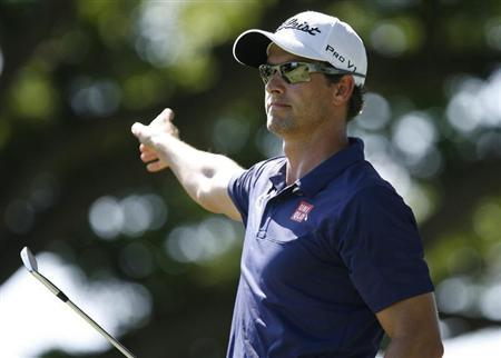 Adam Scott of Australia points as he follows his ball after teeing off on the second hole during the final round of the Sony Open golf tournament at Waialae Country Club in Honolulu, Hawaii.