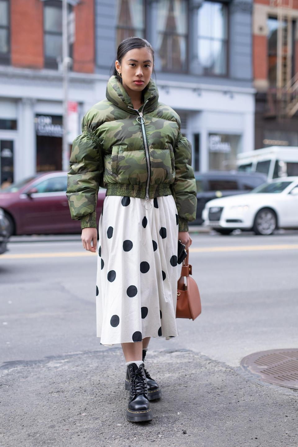 <p>A guest pairs biker boots with a camo jacket and a polka dot skirt during New York Fashion Week. <em>[Photo: Getty]</em> </p>