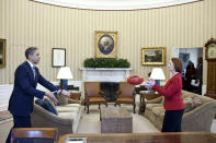 U.S. President Barack Obama practices passing a football with Australia's Prime Minister Julia Gillard in the Oval Office in this picture taken March 7, 2011 and released to Reuters March 8, 2011. Under Australian Football League rules, a player must hold the ball in front of them and punch it with a clenched fist in order to conduct a legal pass to another player. REUTERS/White House/Pete Souza/Handout
