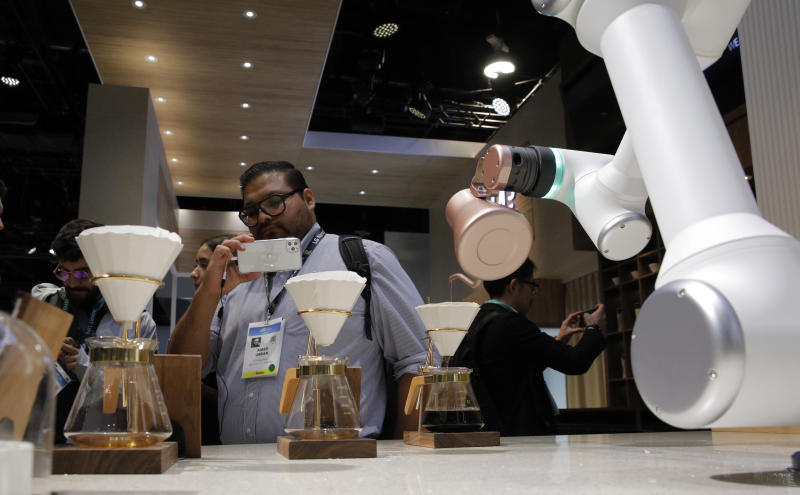 An attendee looks as an LG CLOi CoBot Barista makes coffee in a mock restaurant setting at the LG booth during the CES tech show, Tuesday, Jan. 7, 2020, in Las Vegas. (AP Photo/John Locher)