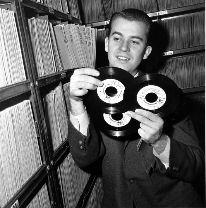 """FILE - In this Feb. 3, 1959 file photo, Dick Clark selects a record in his station library in Philadelphia. Clark, the television host who helped bring rock `n' roll into the mainstream on """"American Bandstand,"""" died Wednesday, April 18, 2012 of a heart attack. He was 82. (AP Photo/File)"""