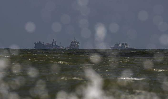 The MV X-Press Pearl, left, is seen pulled by other navel vessels at Kapungoda, where it is anchored off Colombo port on the outskirts of Colombo, Sri Lanka, Wednesday, June 2, 2021. Salvage experts were attempting to tow the fire-stricken container ship that had been loaded with chemicals into the deep sea as the vessel started to sink Wednesday off Sri Lanka's main port, officials said. Water submerged the MV X-Press Pearl's quarterdeck a day after firefighters extinguished a blaze that had been burning for 12 days. (AP Photo/Eranga Jayawardena)