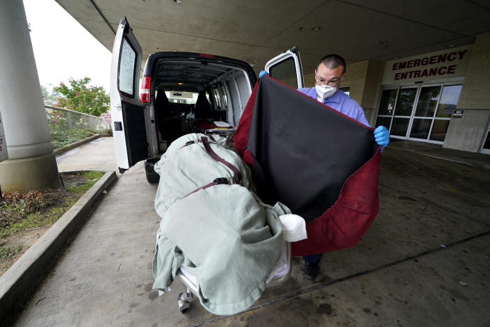 FILE - In this Aug. 18, 2021, file photo, an employee of a local funeral home covers the body of a COVID-19 patient patient who died as he prepares to take it away from a loading dock, at the Willis-Knighton Medical Center in Shreveport, La. COVID-19 deaths in the U.S. have climbed to an average of more than 1,900 a day for the first time since early March, with experts saying the virus is preying largely on a select group: 71 million unvaccinated Americans. (AP Photo/Gerald Herbert, File)