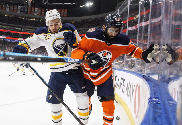 Buffalo Sabres' Zemgus Girgensons (28) checks Edmonton Oilers' Jujhar Khaira (16) during first period NHL hockey action in Edmonton, Alberta, on Monday, Jan. 14, 2019. (Jason Franson/The Canadian Press via AP)
