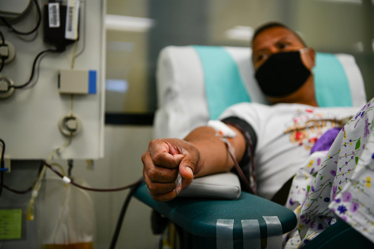 A donor laying on a transfusion chair while wearing a protective mask during the blood donation. Thai Red Cross has requested blood plasma donations from patients recovering from COVID-19. (Photo by Amphol Thongmueangluang/SOPA Images/LightRocket via Getty Images)