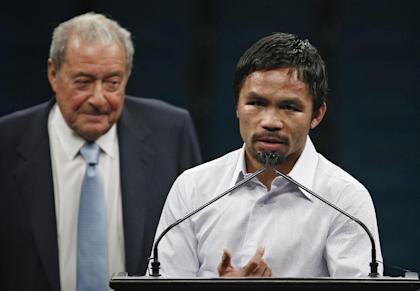 Promoter Bob Arum (L) watches as Manny Pacquiao answers reporters after his fight with Floyd Mayweather. (AP)