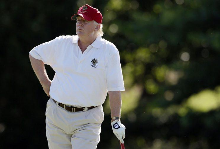 Trump enjoying a round of golf last year (Rex)