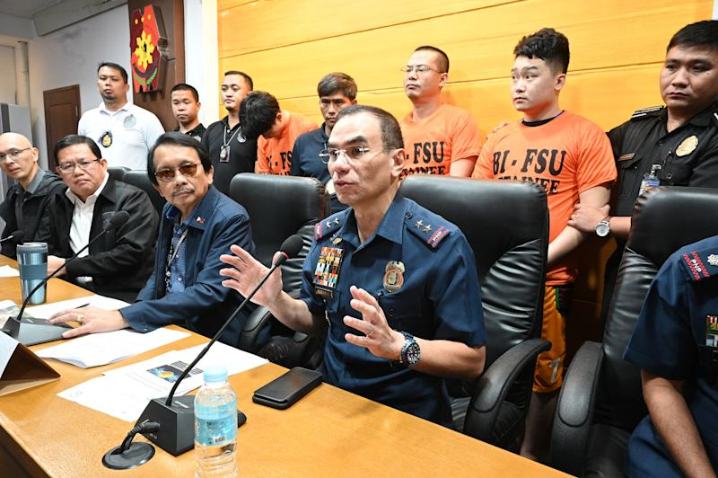 Police capital regional commander Police Major General Guillermo Eleazar (2nd R) gestures while chairman of the Presidential anti-corruption commission Dante Jimenez (3rd L) and Bureau of Immigration deputy commissioner Tobias Javier (2nd L)listen during a press conference where three (back, orange shirts) of the 277 Chinese nationals caught in the act of conducting illegal online operations, were presented to the media in Manila on September 16, 2019. - Philippine police have arrested more than 270 Chinese nationals in a raid on a gang wanted over a vast investment fraud that cost victims in China millions of dollars, authorities said September 13. (Photo by Ted ALJIBE / AFP)        (Photo credit should read TED ALJIBE/AFP/Getty Images)