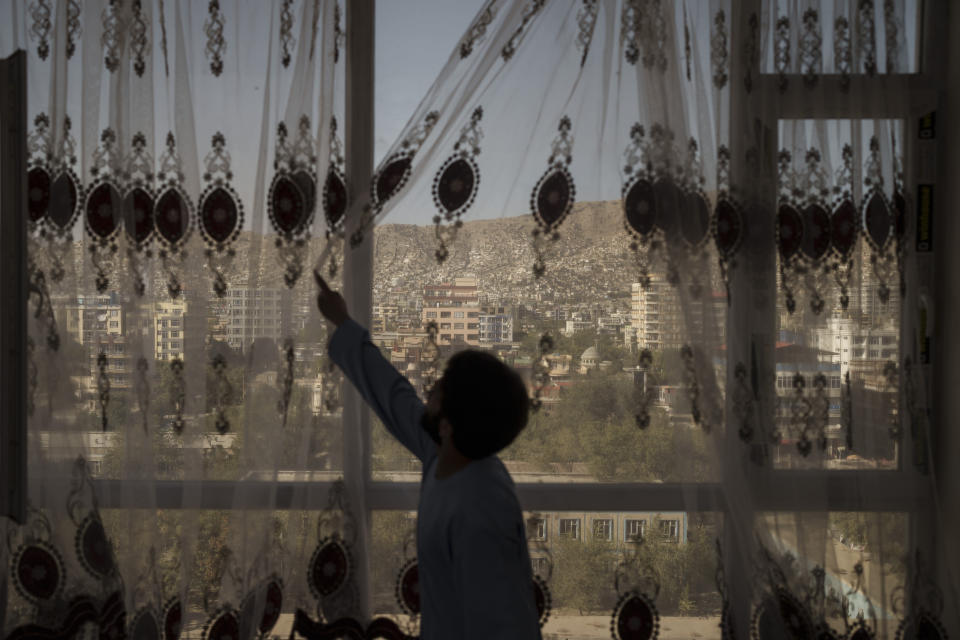 Mohammed Zakir closes the curtains of his family home, overlooking Kabul, Afghanistan, Friday, Sept. 17, 2021. Zakir's bother, Zaki Anwari, was a 17-year-old soccer player who died after trying to board a departing U.S. Air Force aircraft last month. (AP Photo/Felipe Dana)