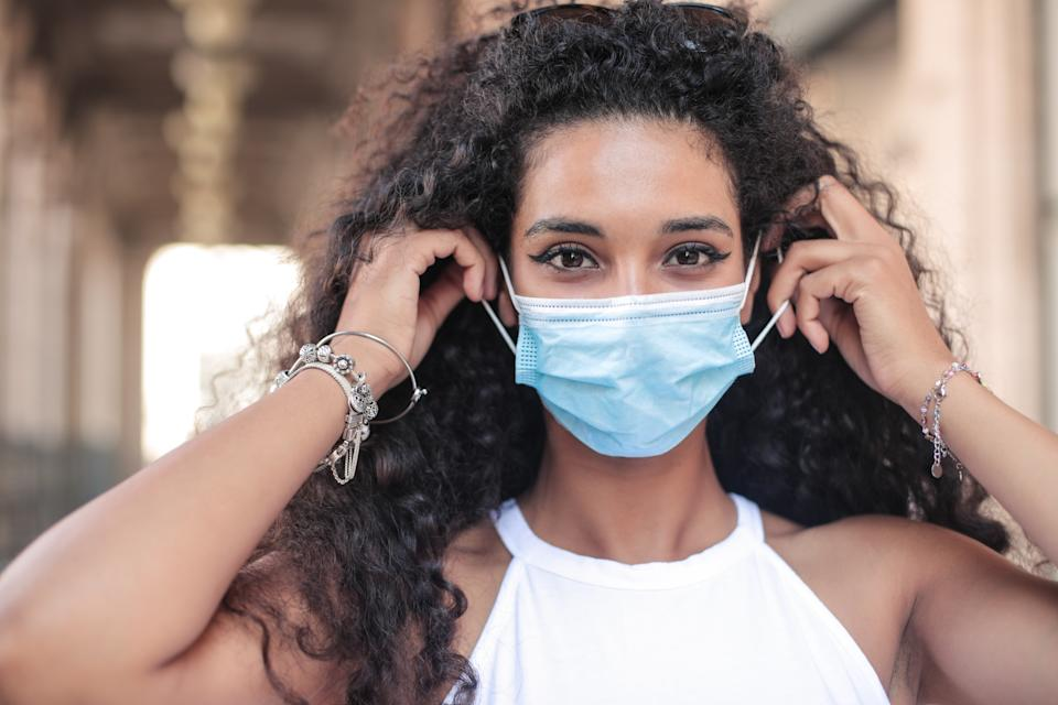 Beautiful young woman wearing surgical mask during covid-19 pandemic lockdown