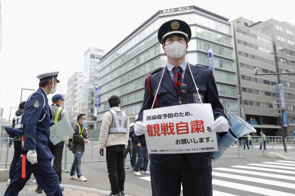 A security guard stands with a note calling for refraining from watching a half-marathon to help curb the spread of the coronavirus in Sapporo, northern Japan, Wednesday, May 5, 2021. The half-marathon was held as a Tokyo 2020 test event three months before the Olympics open. (Masanori Takei/Kyodo News via AP)