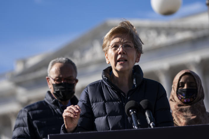 Flanked by Senate Majority Leader Chuck Schumer and Rep. Ilhan Omar, Sen. Elizabeth Warren speaks during a press conference about student debt outside the U.S. Capitol on February 4, 2021, in Washington, D.C. / Credit: Drew Angerer / Getty Images