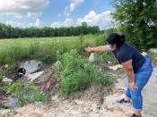 Shirley Ronquillo, a Houston area community activist, points to an open drainage ditch that is blocked by debris and trash on May 27, 2021, in Houston. The ditch, which should remain unobstructed, is located near a subdivision in an unincorporated part of Harris County that has a long history of flooding. (AP Photo/Juan A. Lozano)