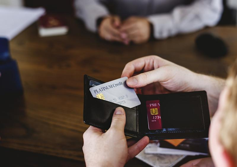 A person taking a credit card out of their wallet to pay for something.