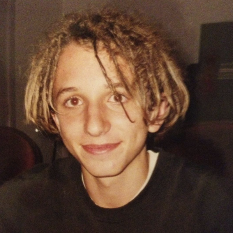 A teenaged Tommy Little wearing a black t-shirt and dreadlocked hair