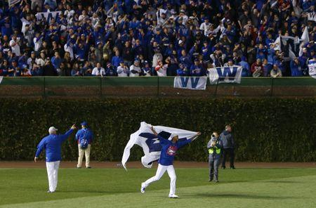 Oct 22, 2016; Chicago, IL, USA; Chicago Cubs relief pitcher Carl Edwards waves a flag in the outfield after defeating the Los Angeles Dodgers in game six of the 2016 NLCS playoff baseball series at Wrigley Field. Mandatory Credit: Jerry Lai-USA TODAY Sports