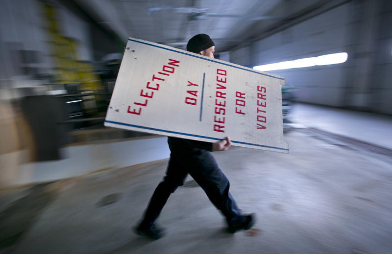 Firefighter Cheyne Hansen takes a sign out of storage at a municipal garage while helping election officials scramble to set up a last-minute polling place, Tuesday, Nov. 4, 2014, in Camden, Maine.  Sunday's snow storm knocked out power to much of the town, including the usual voting location at the public safety building, so officials decided to set up a polling place at a nearby church hall. (AP Photo/Robert F. Bukaty)