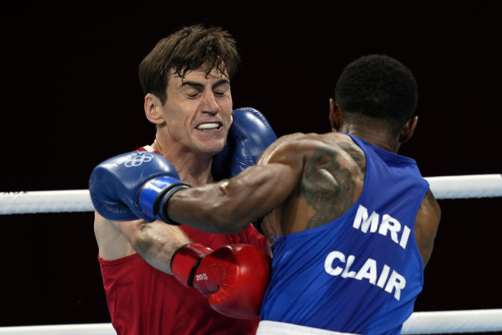 Aidan Walsh, of Ireland, in red, and Merven Clair, of Mauritius, trade punches during their welter weight 69kg quarterfinal boxing match at the 2020 Summer Olympics, Friday, July 30, 2021, in Tokyo, Japan. (AP Photo/Themba Hadebe)