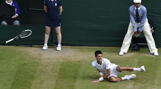 Novak Djokovic of Serbia falls after playing a return to Roger Federer of Switzerland during their men's singles final match at the All England Lawn Tennis Championships at Wimbledon, London, Sunday, July, 6, 2014. (AP Photo/Toby Melville, Pool)