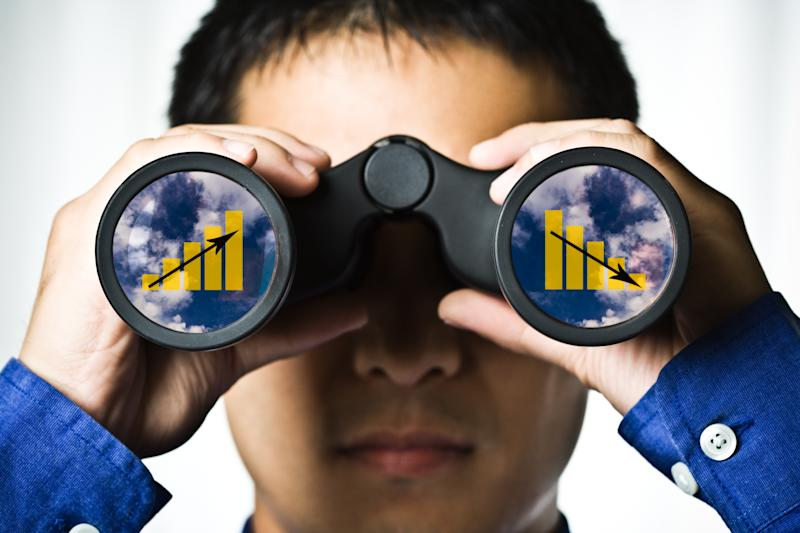 Man holding binoculars with charts going up and down in each of the lenses