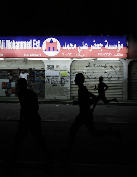 Bahraini anti-government protesters run during clashes with riot police on Sitra, Bahrain, on Sunday, July 29, 2012. Bahrain's Interior Ministry says it is opening investigations into possible rights violations by police during crackdowns on opposition protesters. (AP Photo/Hasan Jamali)