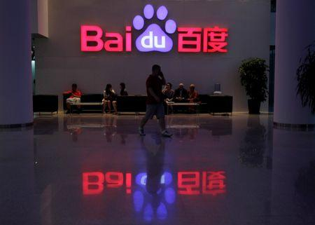 A employee uses his mobile phone as he walks past the company logo of Baidu at its headquarters in Beijing