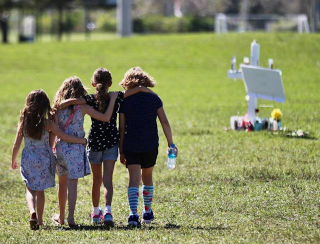 <p>This photo taken Friday, Feb. 16, 2018, shows Four young children with hands around each other as they approach a vigil post at Park Trails Park in Parkland, Fla., on Feb. 16, 2018. (Photo: C.M. Guerrero/The Miami Herald via AP) </p>