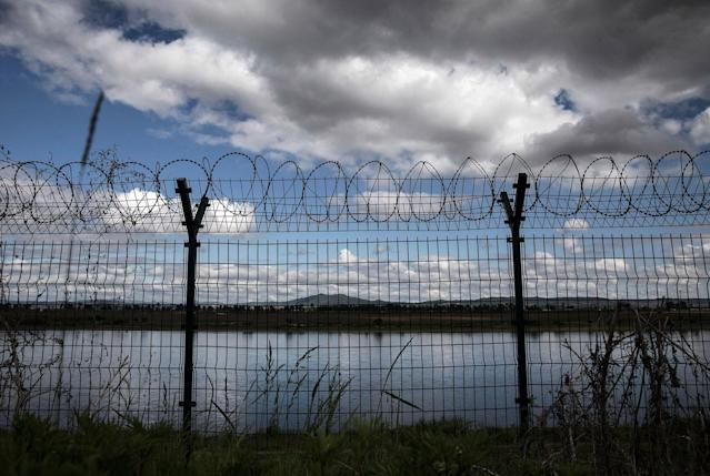 <p>A fence with razor wire is seen protecting the border on the Yalu river north of the border city of Dandong, Liaoning province, northern China across from the city of Sinuiju, North Korea on May 23, 2017 in Dandong, China. (Photo: Kevin Frayer/Getty Images) </p>