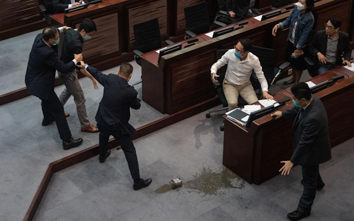 Pro-democracy lawmaker Ted Hui Chi-fung (2-L) is restrained by security guards, after spilling a foul-smelling liquid in the Legislative Council in Hong Kong - JEROME FAVRE/EPA-EFE/Shutterstock/Shutterstock