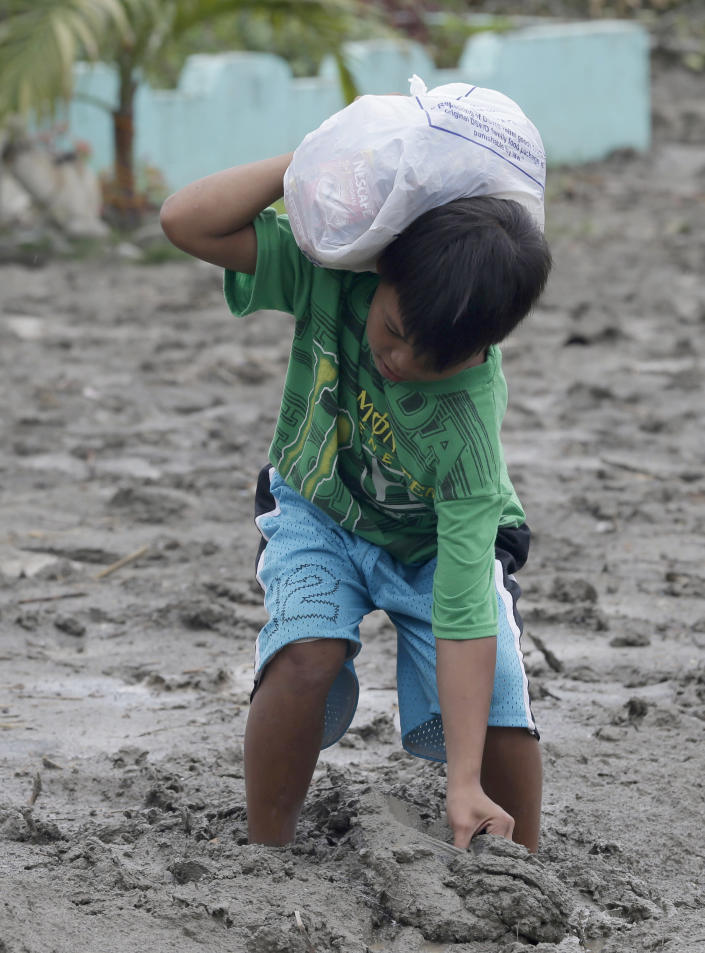 A boy pulls his slippers after getting stuck in the mud as he heads home with relief goods at New Bataan township, Compostela Valley in southern Philippines Friday Dec. 7, 2012. More than 310,000 people have lost their homes since Typhoon Bopha struck Tuesday and are crowded inside evacuation centers or staying with their relatives, relying on food and emergency supplies being rushed in by government agencies and aid groups. (AP Photo/Bullit Marquez)