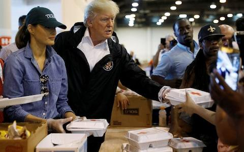 President Donald Trump and first lady Melania Trump help volunteers hand out meals during a visit with flood survivors of Hurricane Harvey at a relief centre in Houston - Credit: Reuters