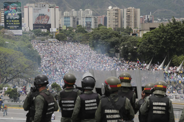<p>Bolivarian National Guards stand on a highway overlooking an anti-government march trying to make its way to the National Assembly in Caracas, Venezuela, Wednesday, May 3, 2017. (AP Photo/Fernando Llano) </p>