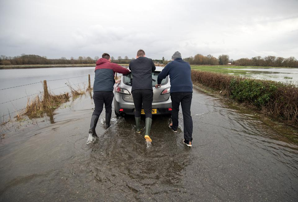 People push a car that was abandoned in floodwater near to Harbridge in Hampshire, in the aftermath of Storm Brendan.