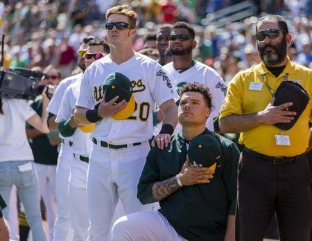 Sep 24, 2017; Oakland, CA, USA; Oakland Athletics catcher Bruce Maxwell (13) kneels during the national anthem as right fielder Mark Canha (20) places his hand on his shoulder before a game against the Texas Rangers at Oakland Coliseum. Mandatory Credit: John Hefti-USA TODAY Sports