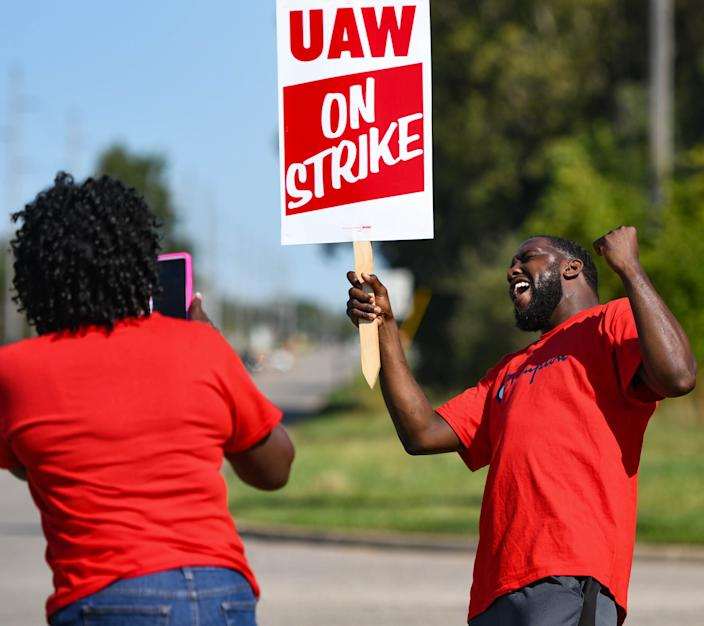 Jacquline Brent takes a picture Wednesday of fellow UAW member Porter Williams while picketing near the GM Lansing Delta Township plant. Brent has worked at GM for 31 years, and Williams for three.