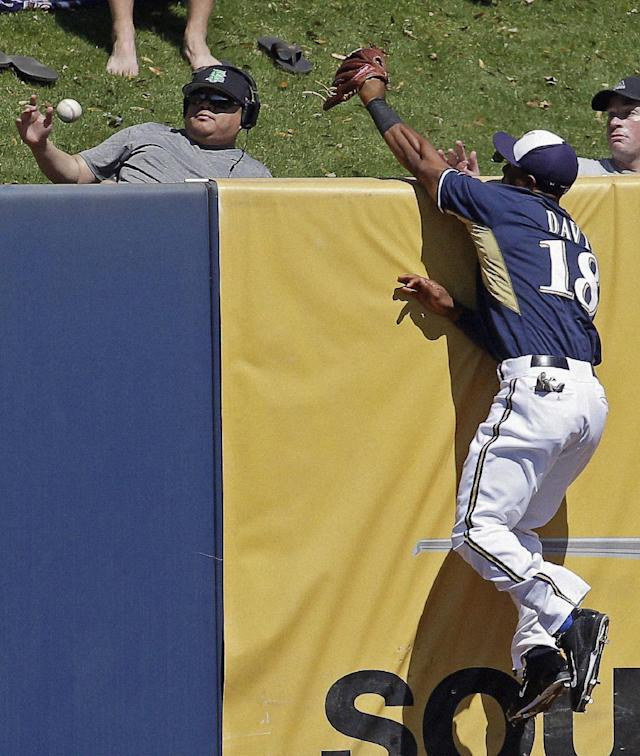 Milwaukee Brewers' Khris Davis (18) leaps but cannot catch a two-run home run hit by Cincinnati Reds' Chris Heisey during the first inning of an exhibition spring baseball game on Saturday, March 15, 2014, in Phoenix. (AP Photo/Morry Gash)