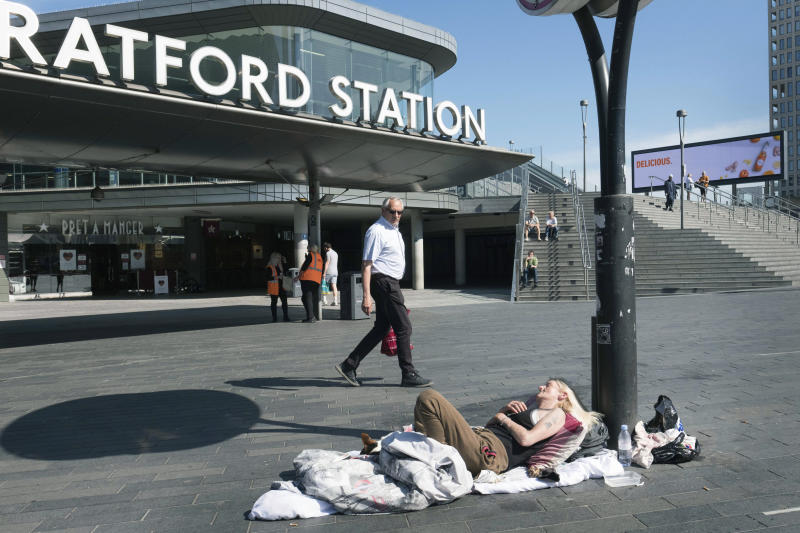 A homeless person lays in the sun outside Stratford Underground Station in London, Wednesday May 20, 2020. (Stefan Rousseau/PA via AP)