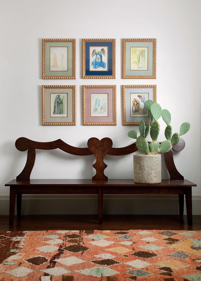 """<div class=""""caption""""> Designer Juniper Tedhams oversaw the soup-to-nuts renovation of her mother Charlotte Herzele's Austin home, a formerly nondescript spec house located on a generous corner lot in a vibrant neighborhood. In the entry, a group of Salvador Dalí watercolors hangs above a custom walnut bench by Erik Gustafson for Juniper Tedhams. The 1940 Berber rug is from FJ Hakimian. </div>"""