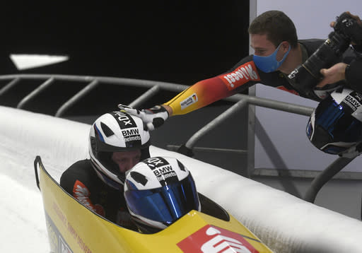 Second placed Johannes Lochner, right, celebrates with first placed Francesco Friedrich and Alexander Schueller, all of Germany, during the two man Bobsled World Cup race in Sigulda, Latvia, Sunday, Nov. 22, 2020. (AP Photo/Roman Koksarov)
