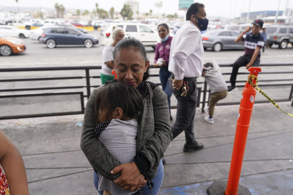 Lizeth Morales, of Honduras, hugs the daughter of a Honduran friend she met at a camp for migrant families as she waits to cross into the United States to begin the asylum process Monday, July 5, 2021, in Tijuana, Mexico. Dozens of people are allowed into the U.S. twice a day at a San Diego border crossing, part of a system that the Biden administration cobbled together to start opening back up the asylum system in the U.S. Immigration advocates have been tasked with choosing which migrants can apply for a limited number of slots to claim humanitarian protection. (AP Photo/Gregory Bull)