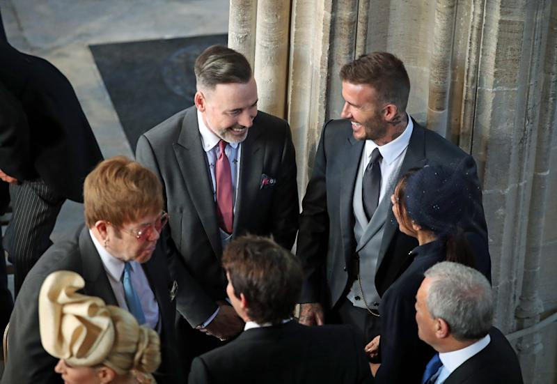 David and Victoria Beckham (both right) talk with Sir Elton John (L) and David Furnish (C) as they arrive in St George's Chapel at Windsor Castle for the wedding of Prince Harry to Meghan Markle on May 19, 2018 in Windsor, England.