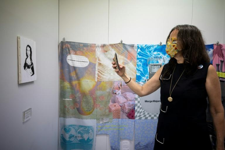 """A woman stands next to """"Self Division"""" (R) by Merge Majurdan as she takes pictures of the painting """"For those who want to steal Mona Lisa"""" by Joji Nakamura"""
