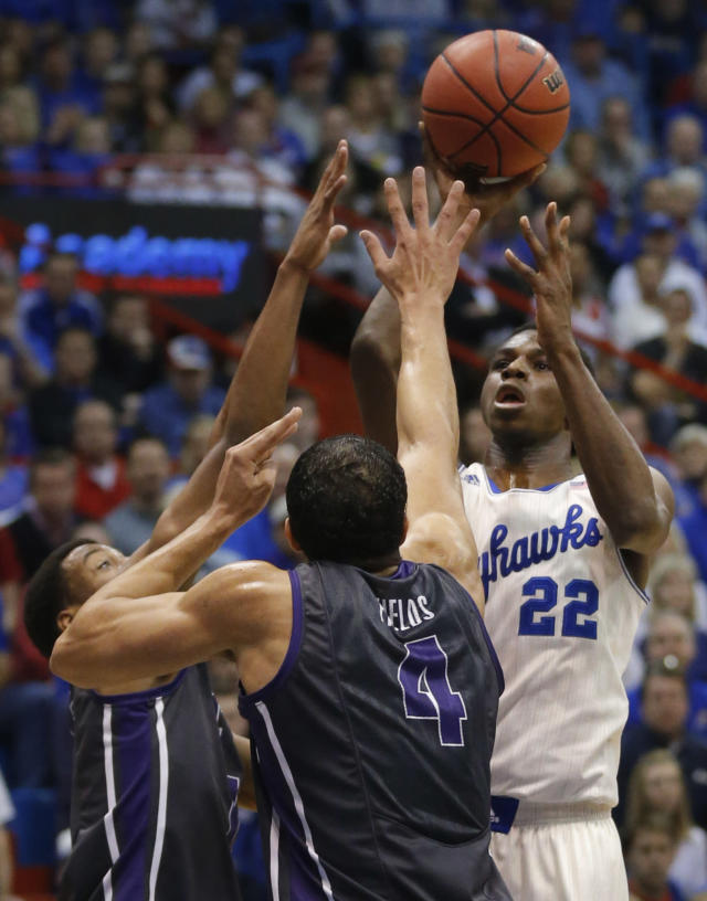 Kansas guard Andrew Wiggins (22) shoots over TCU forward Amric Fields (4) and guard Kyan Anderson, left, during the first half of an NCAA college basketball game in Lawrence, Kan., Saturday, Feb. 15, 2014. (AP Photo/Orlin Wagner)