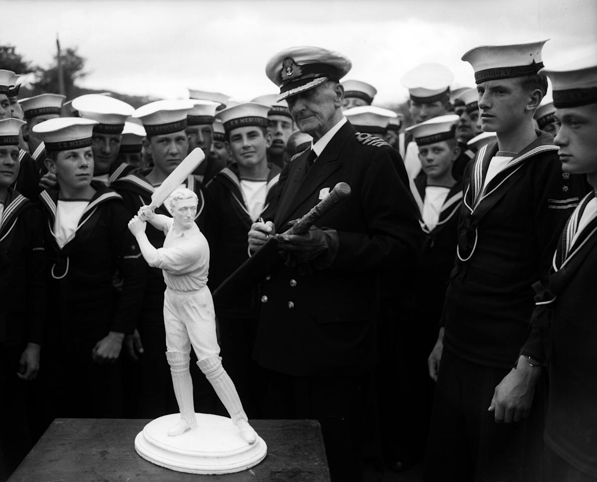 26th June 1950:  Captain C B Fry (Charles Burgess Fry) (1872 - 1956), commander of the training ship Mercury with the crew, inspecting a statuette of himself when a cricketer.  (Photo by Express/Express/Getty Images)