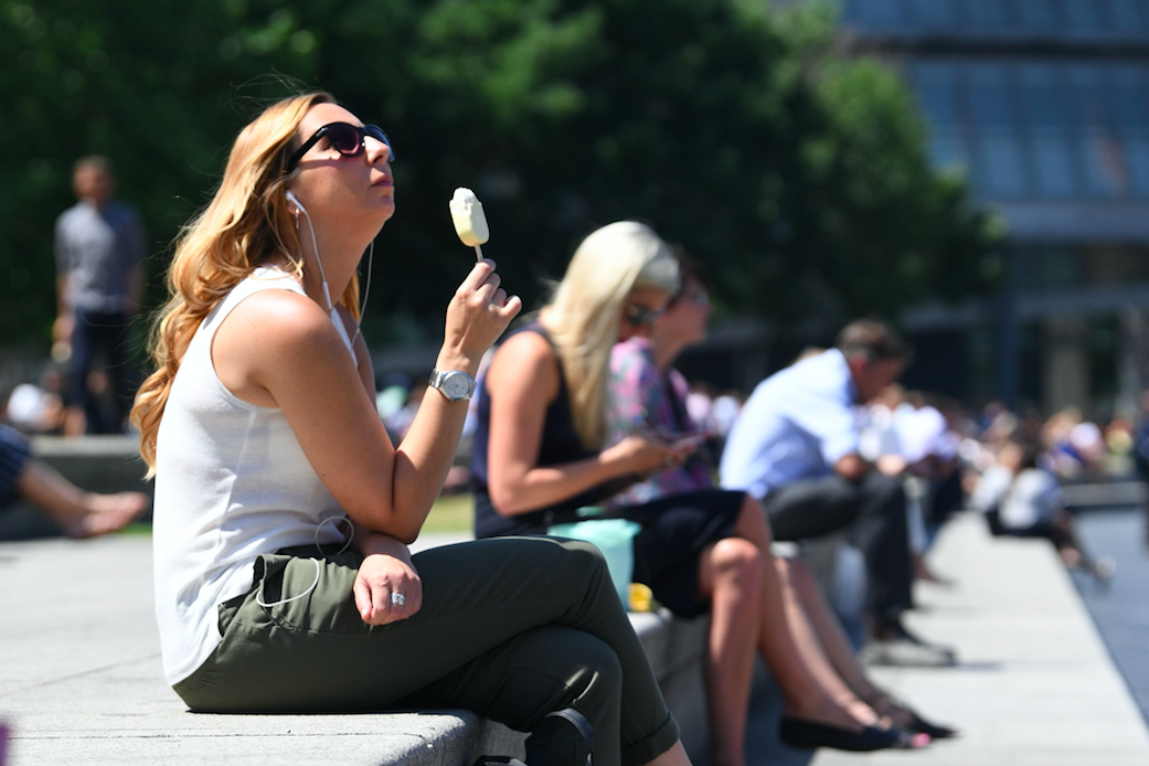 <p>Tourists enjoy the sun whilst they sit on the steps near the Tower of London. (PA) </p>