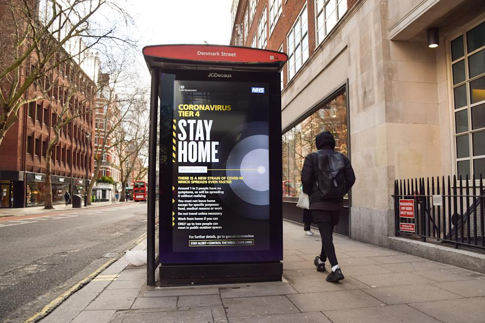 LONDON, UNITED KINGDOM - 2020/12/24: A man walks past a 'Stay Home' coronavirus sign on Charing Cross Road. London has been placed under Tier 4 restrictions as cases surge and new strains of COVID-19 emerge in England. (Photo by Vuk Valcic/SOPA Images/LightRocket via Getty Images)