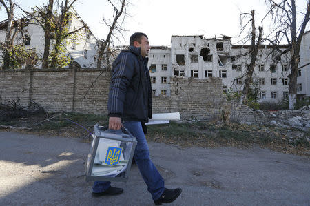 A member of an election commission carries documents and a mobile ballot box as he walks to visit local residents during a parliamentary election in the village of Semyonovka near Slaviansk, eastern Ukraine, October 26, 2014. REUTERS/Vasily Fedosenko