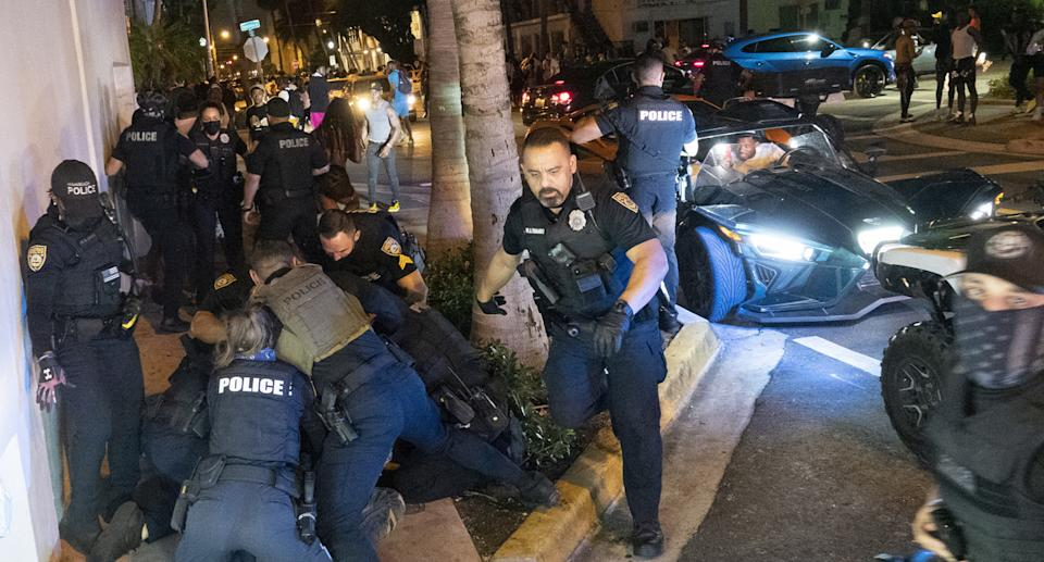 Police fight crowds during spring break in Miami.