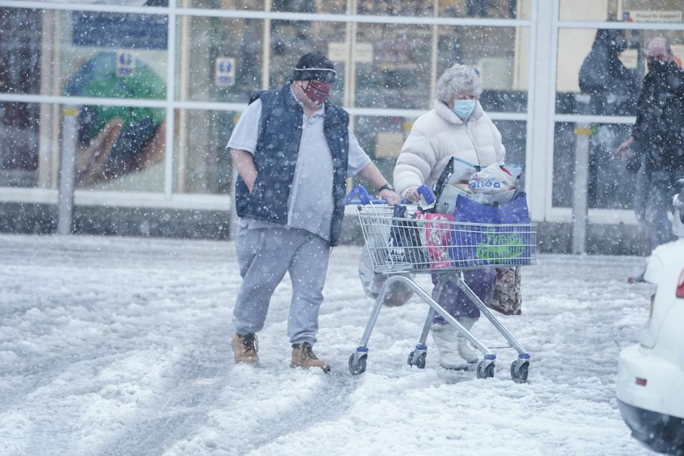 Two people push a shopping trolley through snow in Hexham, Northumberland. Heavy snow and freezing rain is set to batter the UK this week, with warnings issued over potential power cuts and travel delays. (Photo by Owen Humphreys/PA Images via Getty Images)